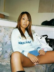 Tanned and slender Asian slut disrobes naked and widens her legs for the camera