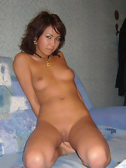A really cute naked Chinese girl spreads her legs for the camera in bed