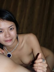 A cute Oriental honey receives nude in bed and gives her boyfriend a handjob