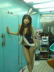 Cute young Oriental babe working as a club hostess in a bunny suit
